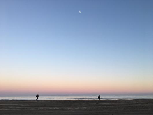 九十九里浜の夕陽 月と釣り人とランニングする人