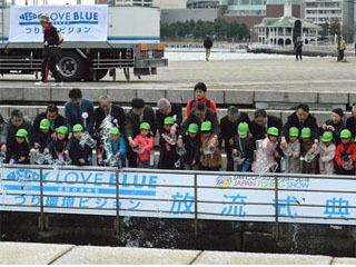 ジャパンフィッシングショーの新たな試みとして近くにある臨港パーク「潮入の池」に地元幼稚園児らがカサゴの稚魚250尾を放流した