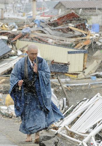 東日本大震災の被災地で祈りながら歩いている僧侶
