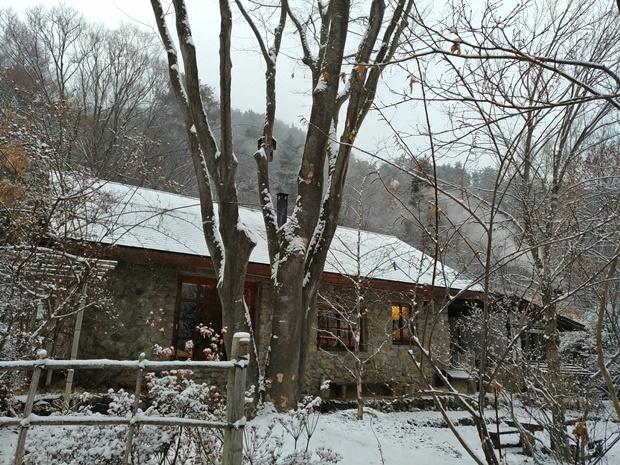 雪の降り始めた石積みの家