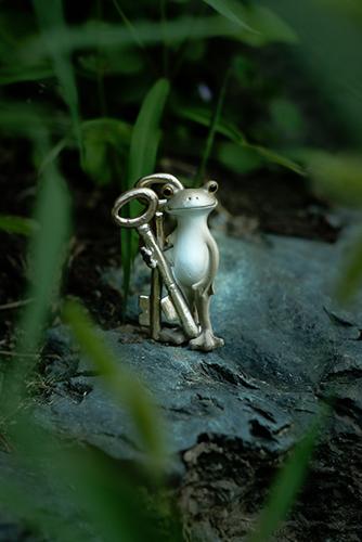 ツバキアキラが撮ったカエルのコポー。草むらの中にたたずむ、セピアカラーのコポタロウ。