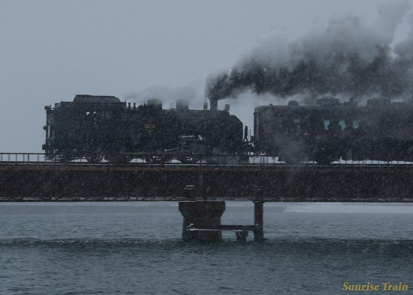 吹雪の中、釧路川を渡るSL冬の湿原号